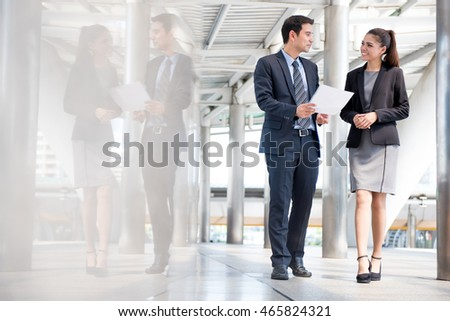 Businessman and businesswoman discussing work while walking