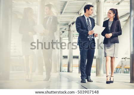 Businessman and businesswoman discussing work while walking, vintage tone effect