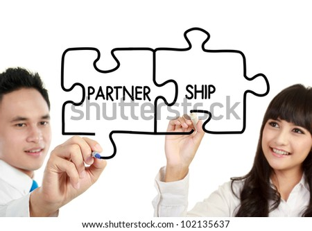 "businessman and businesswoman drawing ""partnership"" written in puzzle"