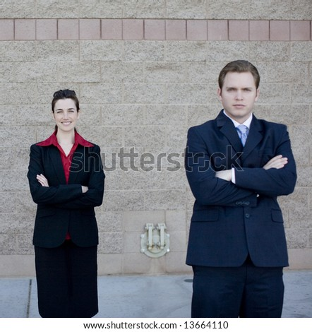 businessman and businesswoman in formal wear standing with arms crossed