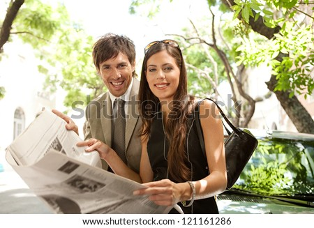 Businessman and businesswoman leaning together on a parked car and sharing a newspaper in a tree aligned street in a classic city, smiling at the camera.