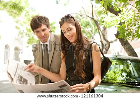 Businessman and businesswoman leaning together on a parked car and sharing a newspaper in a tree aligned street in a classic city.