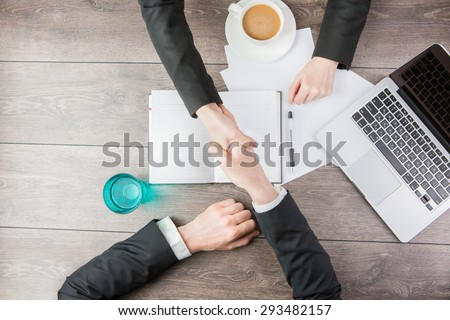 Businessman and businesswoman meeting Handshake. Hand holding. Top view for top managers.  White paper, where you can place your text or information