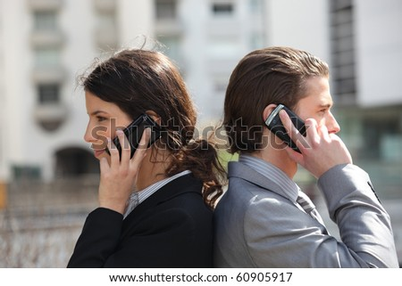 Businessman and businesswoman on phone