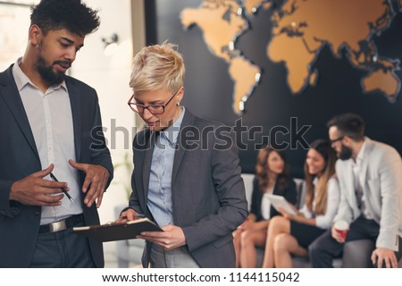 Businessman and businesswoman reviewing contract; business team working in the background. Focus on the man standing