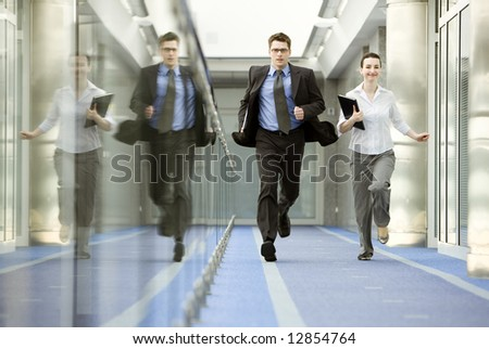 Businessman and businesswoman running on modern office corridor.