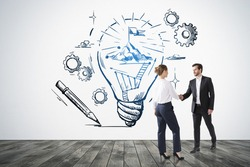 Businessman and businesswoman shake hands, drawing of bulb with mountain top on white wall, parquet floor. Concept of teamwork and success