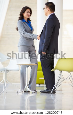 Businessman And Businesswoman Shaking Hands In Modern Office