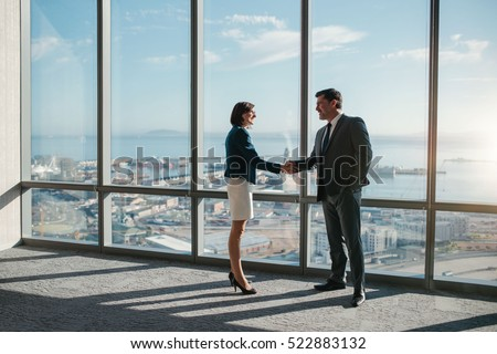 Businessman and businesswoman shaking hands together while standing in front of office building windows overlooking the city