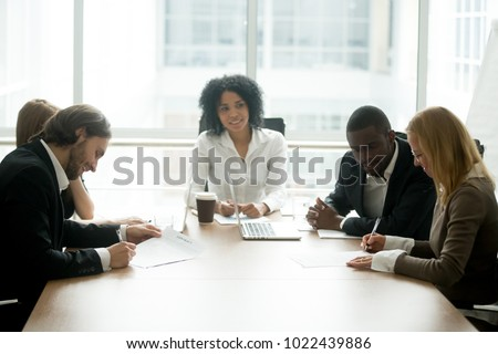 Businessman and businesswoman signing contracts at group multiracial meeting, two smiling male and female new partners making deal after successful negotiations putting signature on business papers