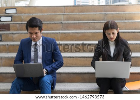 businessman and businesswoman sit on the staircase and working by typing word into laptop, concept of work hard and work anywhere