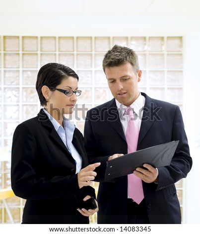 Businessman and businesswoman standing at office in front of glass brick wall and looking at documents.