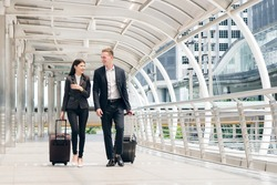 Businessman and businesswoman talking and hold luggage travel to business trip.