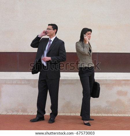 Businessman and businesswoman talking on cell phones