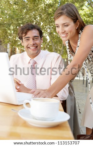 Businessman and businesswoman using a laptop computer while at a coffee shop terrace table outdoors in a classic city.