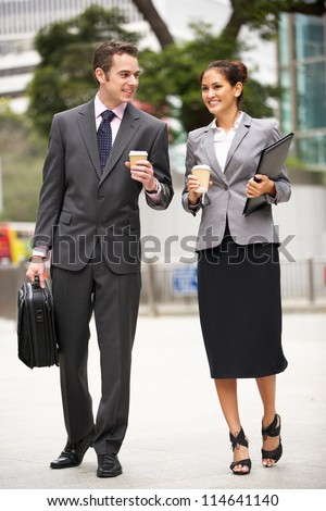 Businessman And Businesswoman Walking Along Street Holding Takeaway Coffee