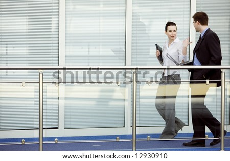 Businessman and businesswoman walking and talking on modern office building corridor.