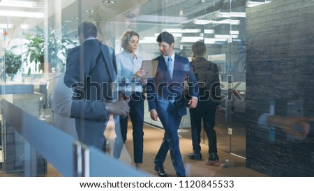 Businessman and Businesswoman Walking Through Glass Hallway, Discussing Work and Using Tablet Computer. Busy Corporate Office Building with Many Workers.