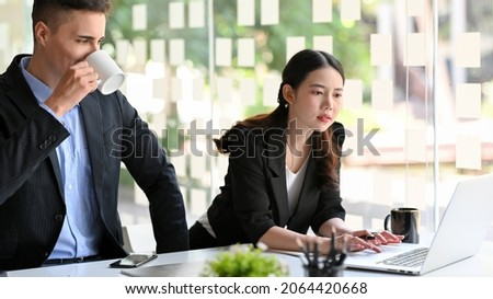 Businessman and businesswoman working on laptop computer together, brainstorming business solutions together as a teamwork.