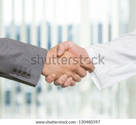 Businessman and doctor shaking hand's in office