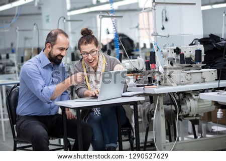 Businessman and fashion designer working on computer in textile factory