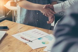 Businessman and partner shaking hands in office