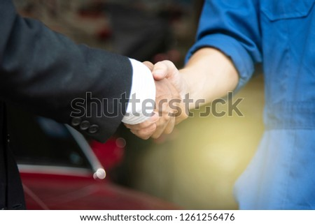 Businessman and repairman are handshaking together to agree the business deal in automobile industry at high standard garage with red car on background using for copy space or customer service