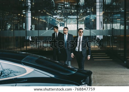 businessman and two bodyguards walking to car Сток-фото ©