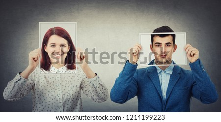 Businessman and woman covering their faces using photo sheets with happy and sad portrait emoticon, like a mask to hide the real emotion from society. Fake identity concept. Introvert vs extrovert.