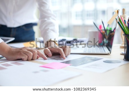Businessman and woman discussing on stock market charts in office #1082369345