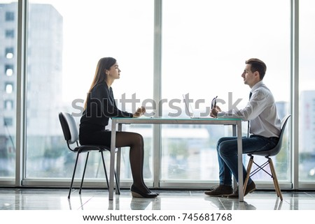 Businessman and woman having a discussion in the office face to face at table