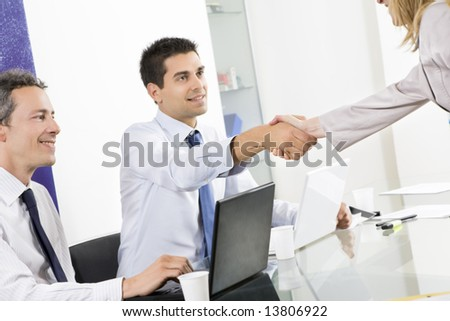 Businessman and woman shaking hands in office with colleague watching.