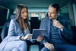 Businessman and woman travelling in vip car transfer. Woman use tablet pc for presentation