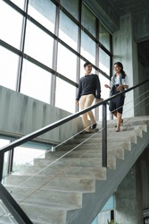 businessman and woman walking downstairs and talking in the office