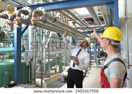 businessman and worker meeting in a factory - maintenance and repair of the industrial plant  #1403367908