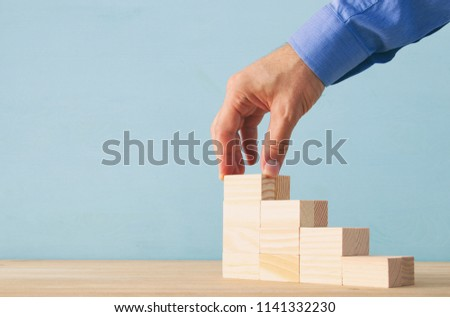 businessman arranging wood blocks stacking as step stairs. success and development concept #1141332230