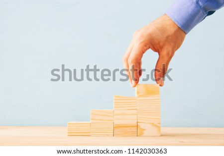 businessman arranging wood blocks stacking as step stairs. success and development concept #1142030363