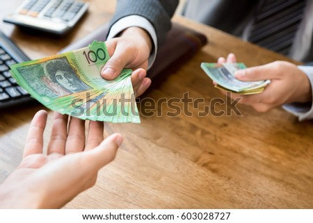 Businessman as an employer paying cash (australian dollar money) to worker at the office - wage, loan and bribery concepts