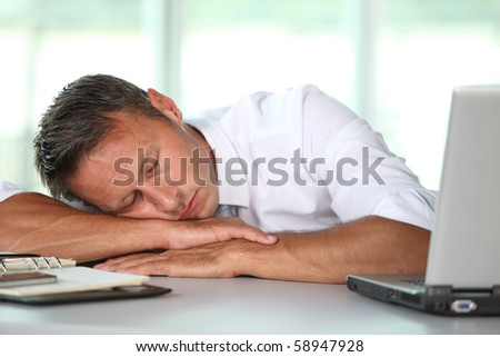 Businessman asleep on his desk