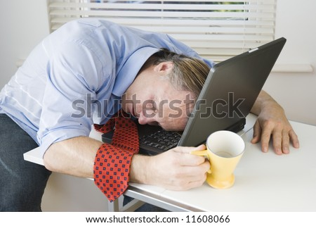 businessman asleep on laptop.