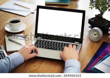 Businessman at a desk in an office typing on a laptop computer with blank white screen ready for content