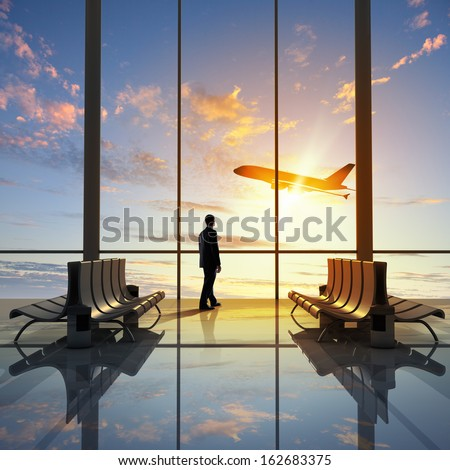Businessman at airport looking at airplane taking off - stock photo