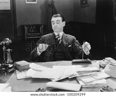Businessman at desk looking at watch