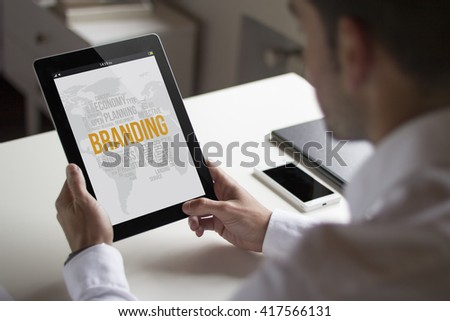businessman at office holding a tablet showing branding. All screen graphics are made up.