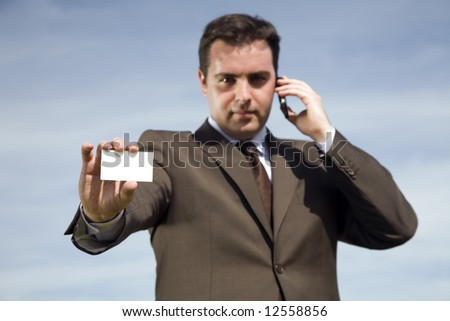 businessman at phone showing his business card (focus on the card)