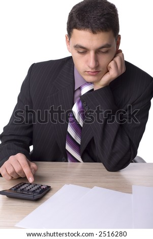 Businessman at the office desk - counting. There are papers and a calculator on the desk. Isolated on white in studio.