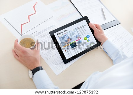 Businessman at the workplace drinking coffee and looking latest business news on modern digital computer.