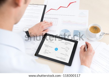 Businessman at the workplace working with documents and using modern digital tablet. Some papers with charts and graphs and cup of coffee on a desktop.