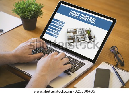 Businessman at work. Close-up top view of man working on laptop home automation. All screen graphics are made up.