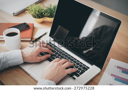 Businessman at work. Close-up top view of man working on laptop while sitting at the wooden desk  #272975228